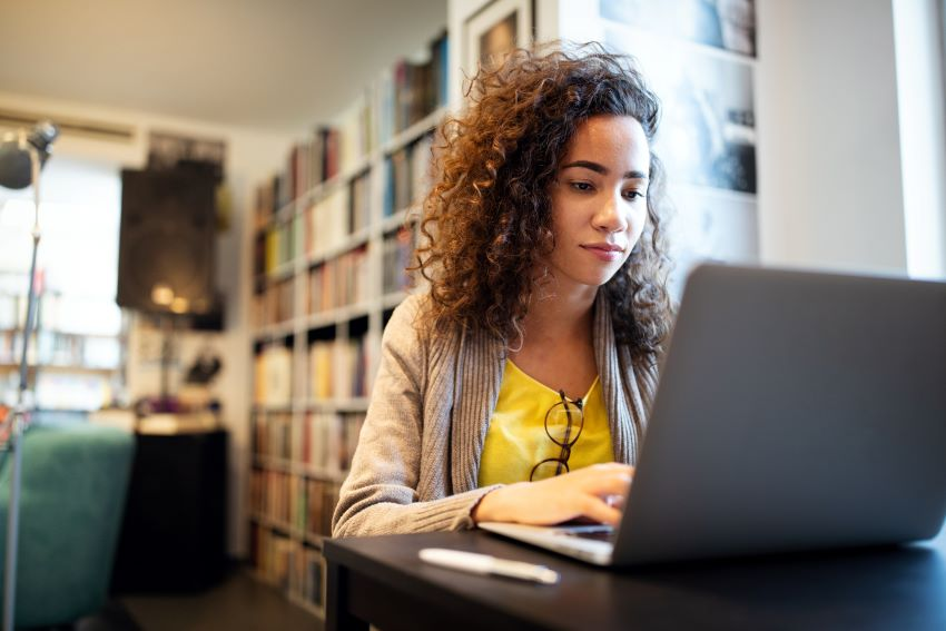 Young woman uses laptop to practice study skills in a college library