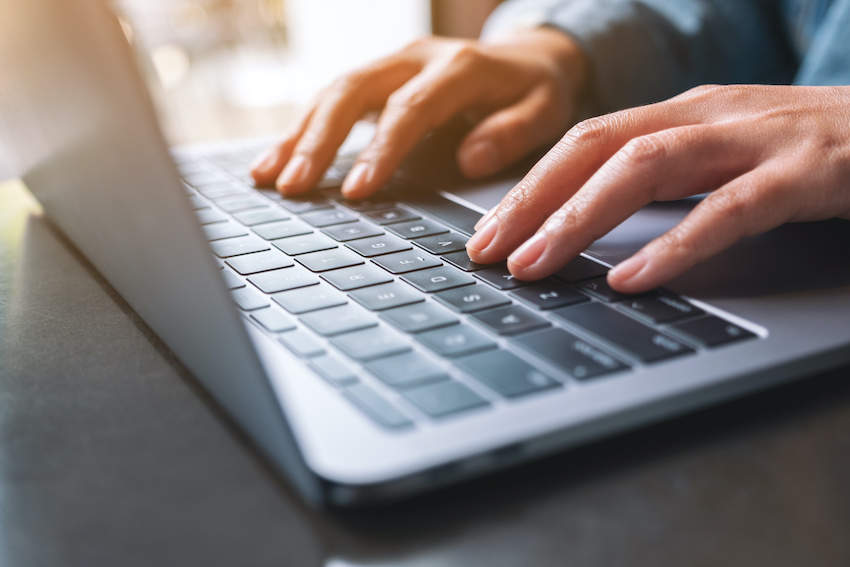 LSAT writing sample: A student's hands type on a laptop