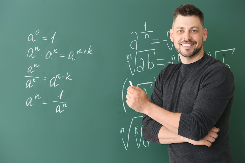 A math tutor stands in front of a chalkboard