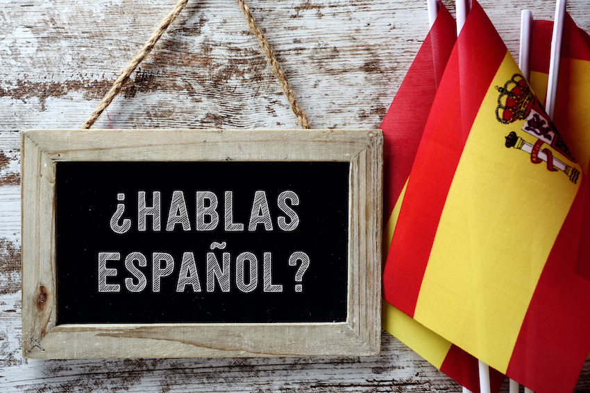 "Spanish flags and a chalk board that reads ""¿Hablas Español?"""