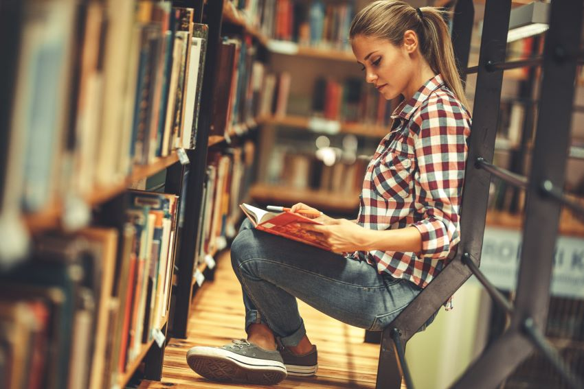 Young woman reading by library shelf