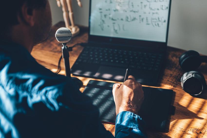 Man teaching online using a laptop with a mic